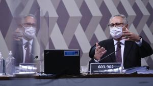 Renan Calheiros, em trajes sociais e máscara, gesticula durante pronunciamento em sua cabine na CPI da Covid-19, com sua imagem refletida pela divisória transparente