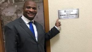 Vereador Sandro do Sindicato, de Duque de Caxias, aponta para placa com seu nome na entrada do gabinete