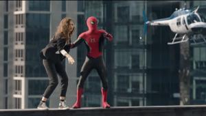 O Homem Aranha segura MJ pelo braço, e os dois se equilibram em uma plataforma a muitos metros de altura, enquanto um helicóptero passa perto deles