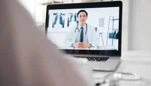 Jovem médico masculino da ásia em uniforme médico branco usando laptop falando por videoconferência com o médico sênior na mesa na clínica de saúde ou hospital.