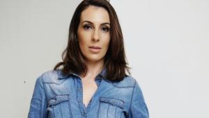 De cabelo castanho no ombro e camisa jeans, Vanessa Rouvier posa para uma fotografia