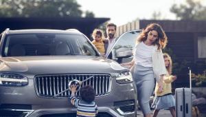 Pai segura bebê no colo, mãe observa o filho brincando na parte dianteira do carro e filha mais velha se dirige para a casa